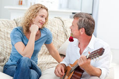 Romantic man playing guitar for her wife at home Stock Photo