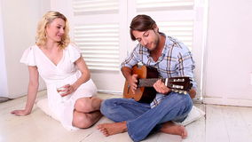 Romantic man playing guitar for his girlfriend. At home in the living room stock video
