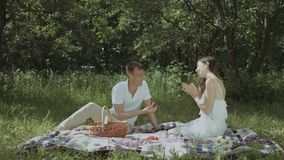 Loving man proposing to his excited girlfriend. Romantic man proposing to his surprised beautiful girlfriend while sitting on blanket in public park during stock video