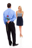 Romantic man rose. Romantic young men hiding a rose behind his back Royalty Free Stock Images