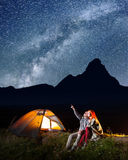 Romantic man showing his lover at the stars and Milky way in the night sky Royalty Free Stock Photo