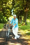 Romantic man standing with bicycle in the park Royalty Free Stock Photos