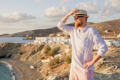 A romantic manly guy with a beard, wearing sunglasses and a hat stands sideways on a rocky shore and looks out to sea. Red-bearded male traveler in a white Stock Images