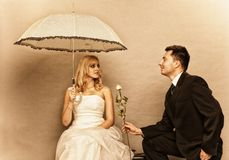 Romantic married couple bride groom on gray background. Wedding day. Portrait of romantic married couple blonde bride with umbrella and enamored groom giving a Stock Photos