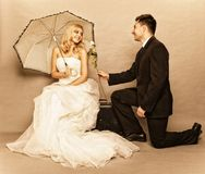 Romantic married couple bride groom vintage photo. Wedding day. Portrait of romantic married couple blonde bride with umbrella and enamored groom giving a rose Stock Image