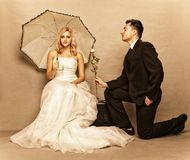Romantic married couple bride groom vintage photo. Wedding day. Portrait of romantic married couple blonde bride with umbrella and enamored groom giving a rose Stock Photos