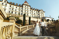 Romantic married couple bride and groom walking down stairs hotel background royalty free stock images
