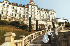 Romantic married couple bride and groom walking down stairs hotel background royalty free stock photography