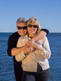 Romantic mature attractive couple at the seaside. Affectionate middle-aged attractive couple at the seaside posing in their sunglasses with the mans arms around Royalty Free Stock Photos