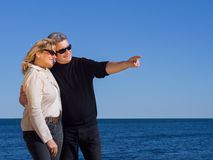Romantic mature couple pointing to copyspace at the coast. Romantic attractive middle-aged mature couple in stylish clothes and sunglasses standing pointing to Royalty Free Stock Photo