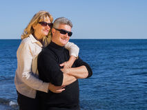 Romantic mature couple relaxing at the seaside. Romantic attractive middle-aged mature couple relaxing at the seaside in an affectionate embrace standing looking Stock Images