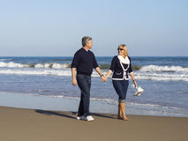 Romantic mature couple walking along the beach stock images