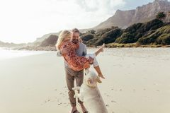 Free Romantic Mature Couple With A Dog On The Beach Royalty Free Stock Images - 116451099