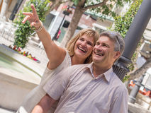 Romantic mature couple with woman pointing out in holidays. Romantic mature attractive couple pointing out something amusing to her husband as they stand close Stock Photography