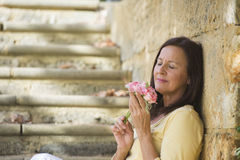 Romantic mature woman in love with rose Stock Photo