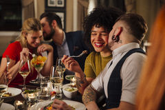 Romantic Meal Out. Man is kissing his partner on the cheek while they are dining at a restaurant with other friends. Another couple can be seen out of focus in stock images