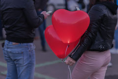 Romantic meeting of guy and girl. Two LED balloons in form of scarlet burning hearts in evening in girl`s hand.Romantic Stock Images