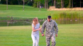 Romantic meeting of soldier with girlfriend in the park. stock footage