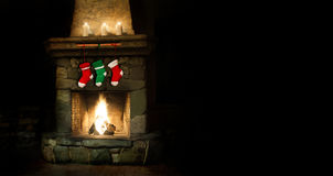 Romantic merry christmas postcard template. colorful stockings on fireplace collage. green red socks for gifts. Xmas. Interior with chimney place, candles. Copy Stock Images