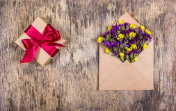 Romantic message. A living letter. Wild flowers in the envelope and a box with a gift. Copy space. Romantic message. A living letter. Wild flowers in the Stock Image