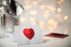 Romantic message note with red 3d heart on it, and champagne with glasses and fairy light strings with heart bokeh in the backgrou. A white message note with a stock photography