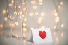 Romantic message note with red 3d heart on it, and champagne with glasses and fairy light strings with heart bokeh in the backgrou. A white message note with a stock photos