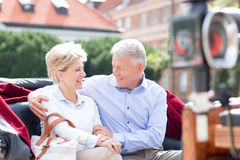 Romantic middle-aged couple sitting in horse cart Stock Photos