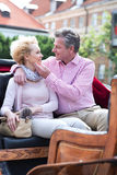 Romantic middle-aged couple sitting in horse cart Stock Images
