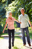 Romantic Middle Aged Couple Walking Along Countryside Path Stock Image