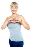 Romantic middle aged woman gesturing heart shape Royalty Free Stock Images