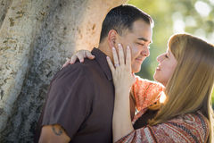 Romantic Mixed Race Couple Embracing Leaning Against Tree Stock Images