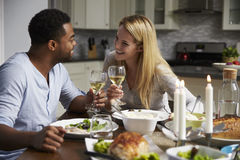 Romantic mixed race couple making a toast at meal in kitchen Stock Photo