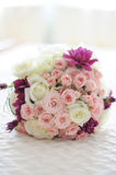 Romantic mixed round wedding bouquet. Floral arrangement ideas for the bride-to-be. A soft colored wedding bouquet positioned on a white silky cushion Stock Image