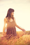 Romantic Model in Sun Dress in Golden Field at Sunset Royalty Free Stock Photos