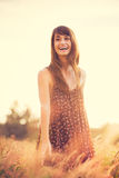 Romantic Model in Sun Dress in Golden Field at Sunset Royalty Free Stock Image