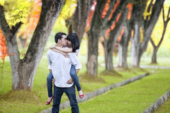 Romantic moment in autumn. Portrait of romantic young couple with handsome boy carry pickaback his girlfriend in autumn day Royalty Free Stock Photo