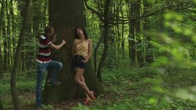 Romantic moment of love. Young beautiful couple in love carving a heart with their initials on a tree. Green spring. Forest background stock footage