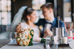 Romantic moment of newlywed couple. Stylish young groom and his beautiful bride holding each other. Wedding bouquet stock photo