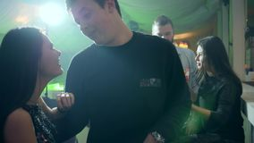 Romantic moments, beautiful young couple on background of bright lights in club stock footage