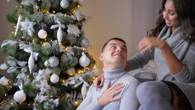 Romantic moments on eve of new year, woman gently hugs her man at home. Romantic moments on the eve of new year, woman gently hugs her man at home stock footage