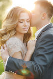 Romantic moments of a young wedding couple on summer meadow Stock Photo