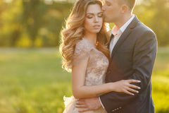 Romantic moments of a young wedding couple on summer meadow Stock Photos