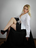 Romantic mood. Blond woman in white shirt and black mini skirt sitting Royalty Free Stock Photos