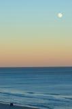 Romantic Moon. A couple strolls under the moon on Hilton Head Island Beach as the sun is setting royalty free stock photo