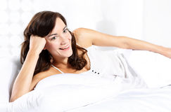 Romantic morning. Beautiful woman resting in a soft, white linen Stock Photography