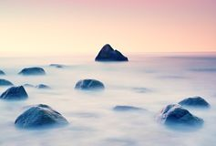 Romantic morning at sea. Big boulders sticking out from smooth water level. Pink horozon with first hot sun rays. Stock Image
