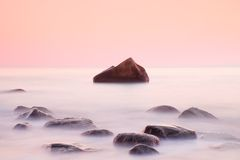 Romantic morning at sea. Big boulders sticking out from smooth water level. Pink horozon with first hot sun rays. Stock Photography