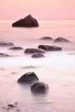 Romantic morning at sea. Big boulders sticking out from smooth wavy sea. Long exposure. For smooth dreamy water level Stock Images
