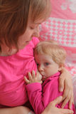 Romantic motherhood. Picture of young happy mother breastfeeding little baby in pink colors Stock Image