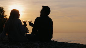 Romantic multi-ethnic couple drinking wine on the beach or lake. One can see their silhouettes behind at sunset. Asian. Multiethnic couple relaxing with wine stock video footage